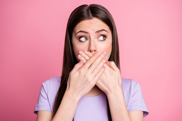 Closeup photo of attractive shocked lady close mouth hands look terrified side empty space said wrong bad thing secret wear casual violet t-shirt isolated pink pastel color background