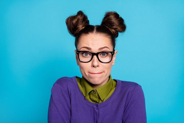 Closeup photo of attractive terrified student lady two funny buns pressing lips did wrong thing made mistake feel sorry wear shirt collar violet sweater isolated blue color background