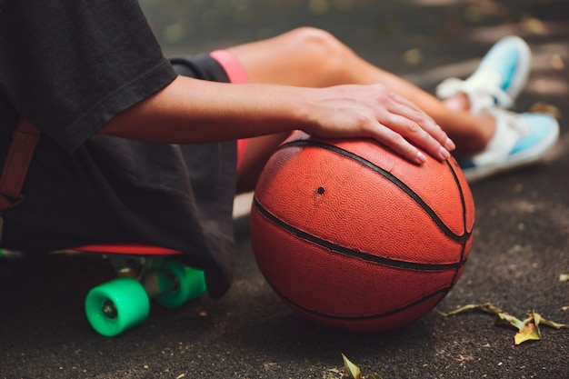 Closeup photo basketball ball with girl sitting on plastic orange penny shortboard on asphalt