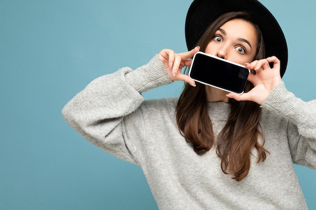 Closeup photo of beautiful positive woman person wearing black hat and grey sweater holding mobilephone showing smartphone isolated on background looking at camera