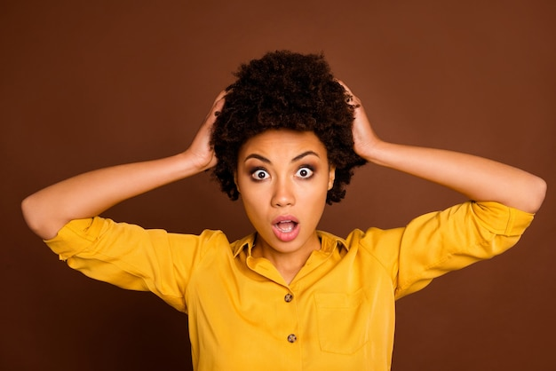 Closeup photo of beautiful pretty dark skin curly lady hold arms on head stressed need to work at weekend bad awful news stupor wear yellow shirt isolated brown color