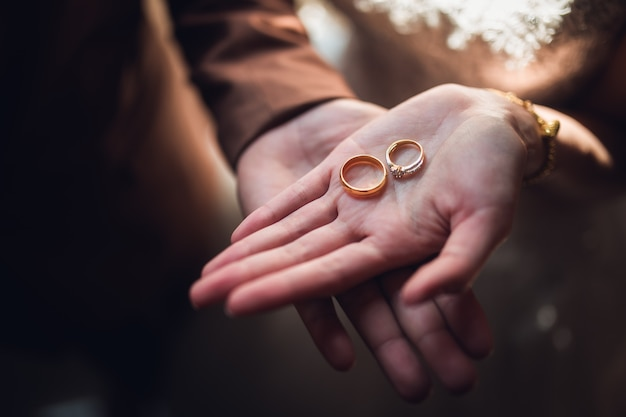 Closeup photo of bride and groom holding golden wedding rings on hands
