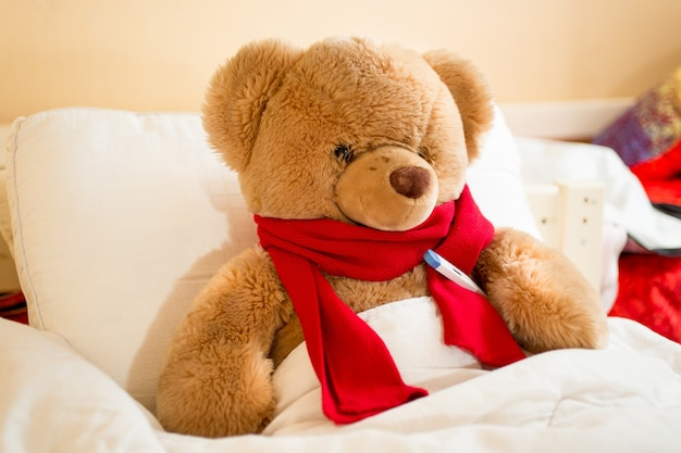 Closeup photo of brown teddy bear in read scarf lying in bed with thermometer