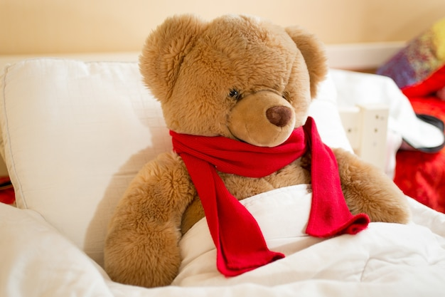 Closeup photo of brown teddy bear in red scarf lying in bed