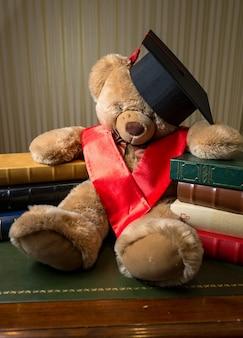 Closeup photo of brown teddy bear wearing graduation cap leaning on books