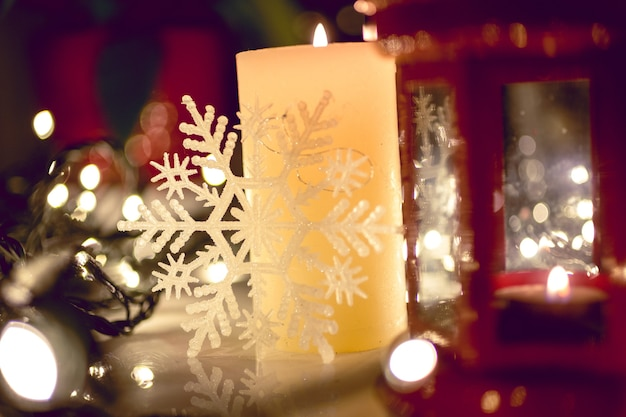 Closeup photo of burning candle on decorated christmas table