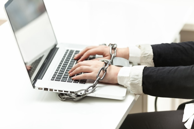 Closeup photo of businesswoman locked to laptop by chain