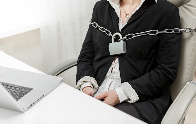 Closeup photo of businesswoman tied to chair by metal chain