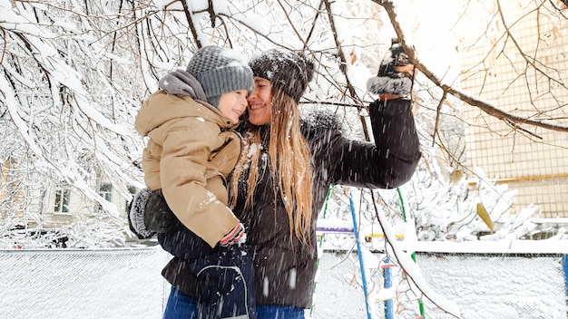 Closeup photo of cheerful young mother with her cute son in jacket and hat playing with snow covered tree on the playground in the park