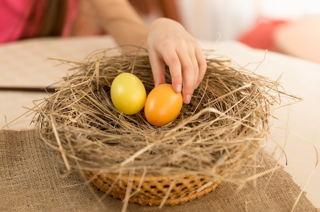 Closeup photo of child hand picking easter egg from the nest