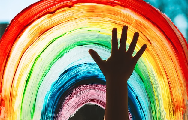 Closeup photo of childs hands touch painting rainbow on window family life background