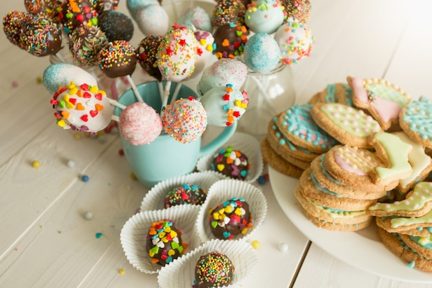 Closeup photo of colorful cake pops and cookies with icing