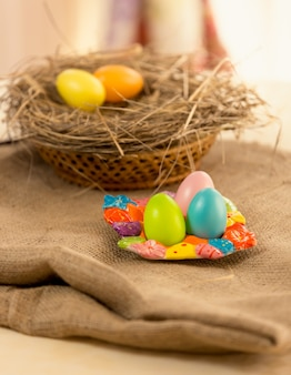 Closeup photo of colorful easter eggs lying on table covered with burlap