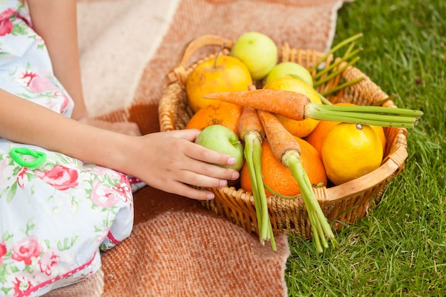Closeup photo of cute girl at picnic with basket of fruits and vegetables