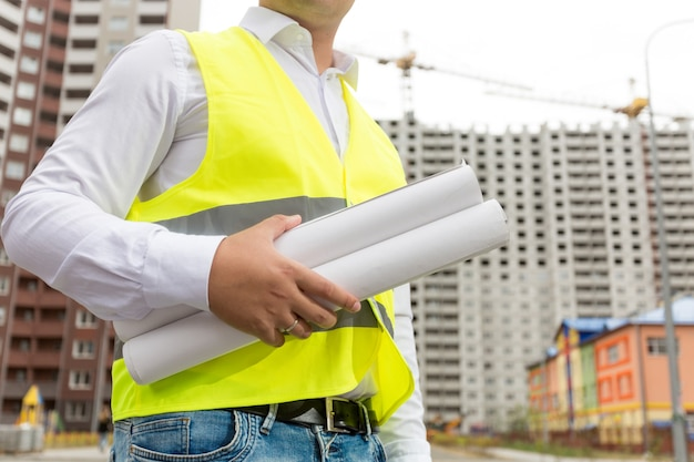 Closeup photo of engineer holding rolled blueprints in building site