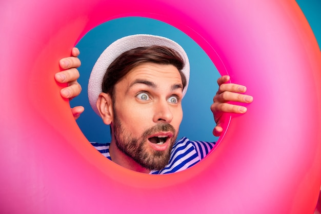 Closeup photo of excited interested funny guy open mouth tourist look inside pink rubber float lifebuoy see sale prices wear striped sailor shirt cap isolated blue color