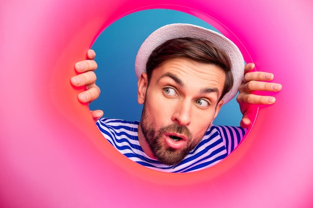 Closeup photo of excited interested funny guy tourist look side inside pink rubber float lifebuoy see sale shopping wear striped sailor shirt cap isolated blue color