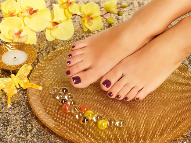 Closeup photo of a female feet at spa salon on pedicure procedure. legs care concept.