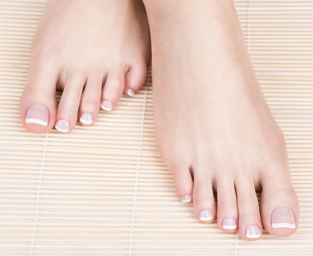 Foto del primo piano di un piede femminile con il pedicure francese bianco sulle unghie