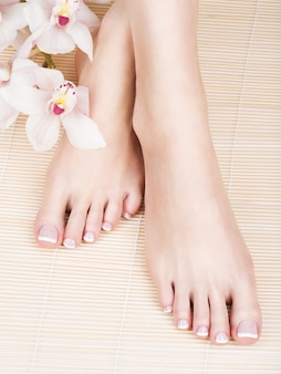 Closeup photo of a female feet with white french pedicure on nails