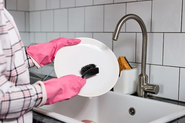 Closeup photo of female hands in pink rubber gloves washing dinner plate with dish brush