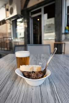 Closeup photo of a fresh beer in a glass and an aperitif of pork cheeks on the terrace of a spanish bar