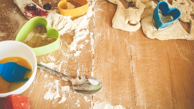 Closeup photo of fresh dough, eggs, milk, and lots of tools for bakery and cooking lying on the big wooden kitchen counterboard