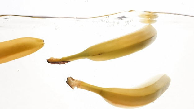 Closeup photo of fresh ripe yellow bananas falling and splashing in clear water against isolated white backgorund