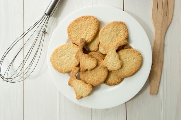 白い机の上にクッキーと台所用品と皿の上からのクローズアップ写真