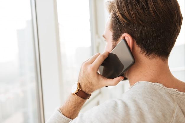 짧은 검은 머리는 검은 휴대 전화에 휴대 전화를하면서 창을 통해 찾고 남자의 뒤에서 근접 촬영 사진