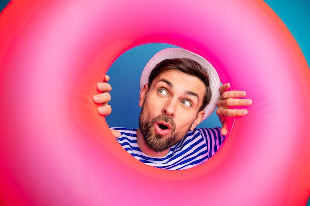 Closeup photo of funky excited handsome guy tourist look inside colorful pink rubber lifebuoy see low prices shopping wear striped sailor shirt cap isolated blue color