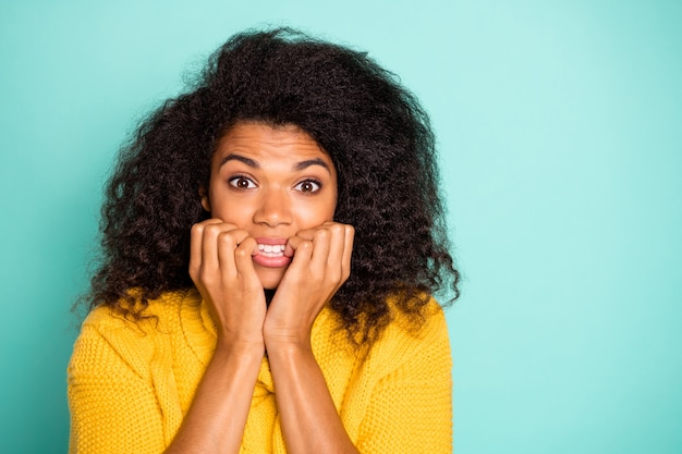 Closeup photo of funny dark skin lady holding fingers in mouth nervous about made mistake wear yellow knitted jumper isolated blue teal color wall