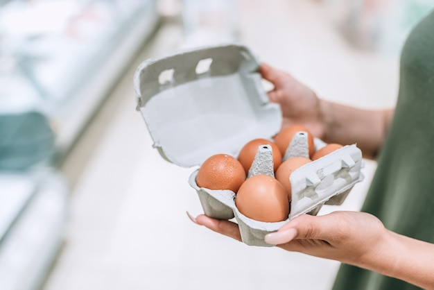 Closeup photo of a girl holding cardboad box with eggs.