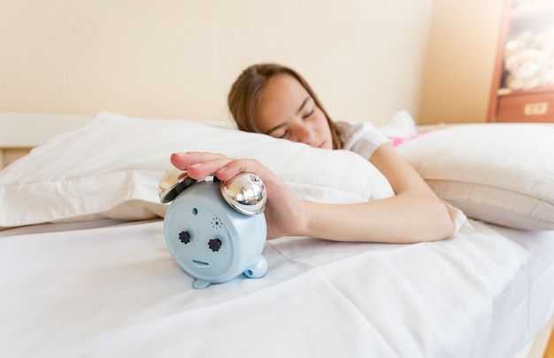 Closeup photo of girl reaching for alarm clock