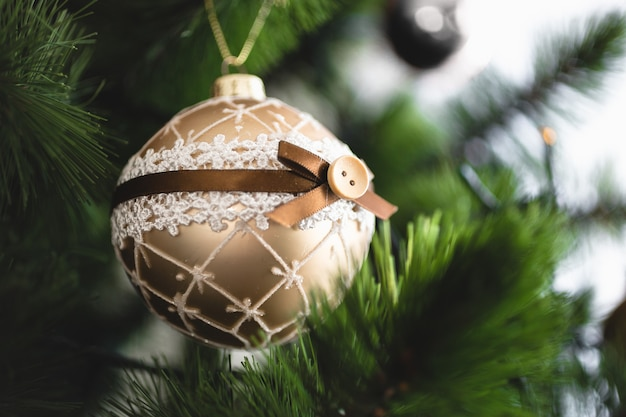 Closeup photo of golden ball on christmas tree