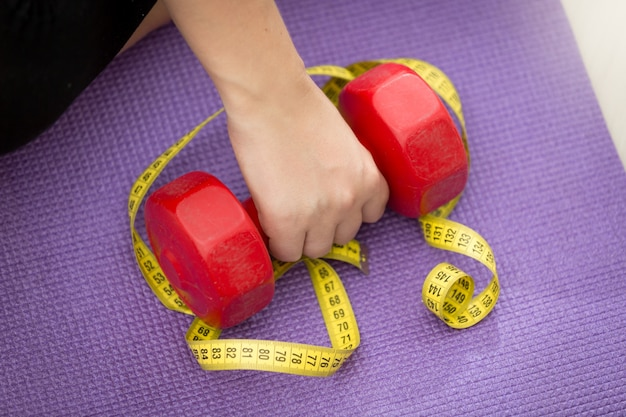 Closeup photo of hand lifting dumbbell covered by measuring tape