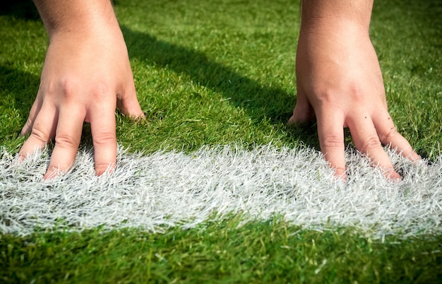 Closeup photo of hands on white start line drawn on grass