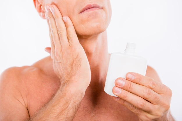 Closeup photo of a handsome shaved man smearing lotion after shave