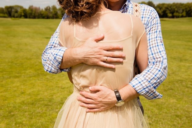 Closeup photo of a happy couple in love huging in a park