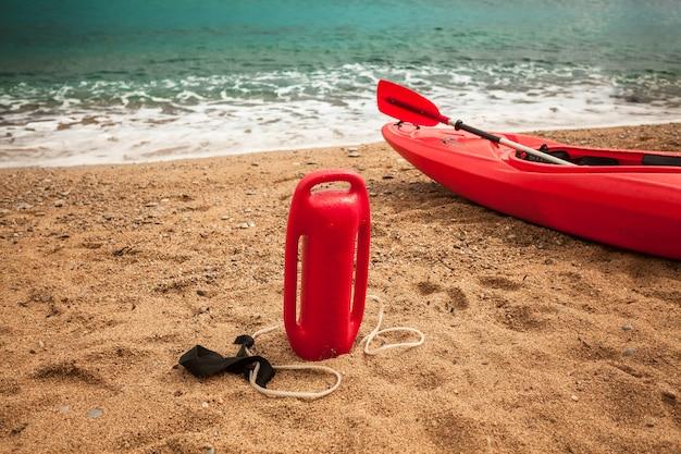 Closeup photo of life saving buoy and lifeguard kayak on sand beach