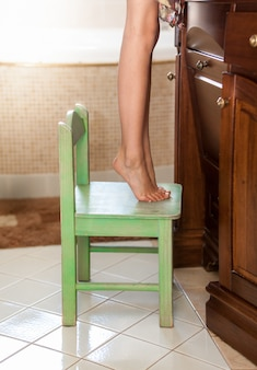 Closeup photo of little girl standing on tiptoes on chair at bathroom