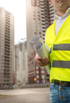Closeup photo of male construction engineer posing at high building at sunny day