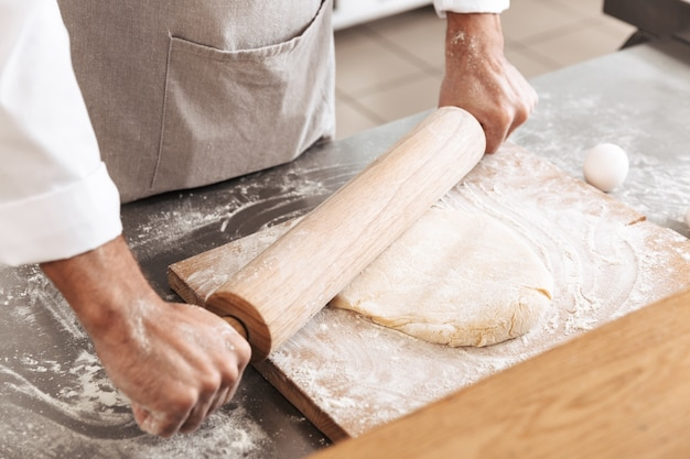 Closeup photo of male hands making dough for pastry with wooden rolling pin, on table at bakery or kitchen