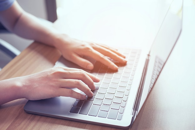Closeup photo of male hands typing on laptop