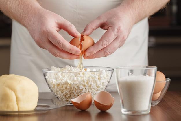 Closeup photo of man breaking egg in glass bowl