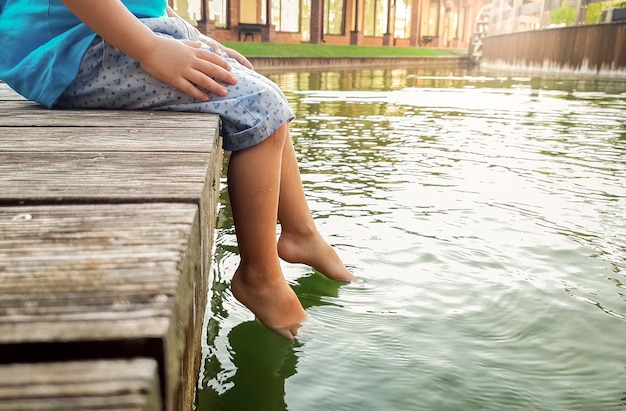 Крупным планом фото 3-летнего маленького мальчика, сидящего на деревянной пристани и держащего ноги в речной воде. ребенок плещется в озере с ног