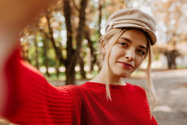 가을 공원에서 아름다운 셀카를 만드는 빨간 스웨터에 매력적인 금발의 근접 촬영 사진. 자연스러운 메이크업 세련 된 가벼운 모자에 야외 포즈와 화려한 젊은 여자.