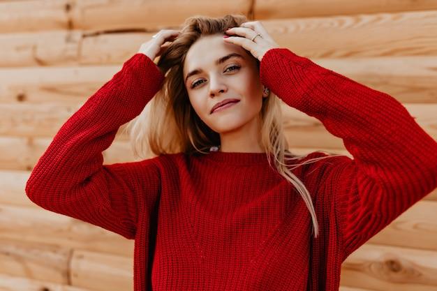 Крупным планом фото очаровательной девушки, нежно улыбаясь в деревянной стене.