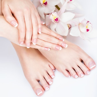ペディキュアとマニキュアの手順に関するスパサロンでの女性の足のクローズアップ写真-ソフトフォーカス画像