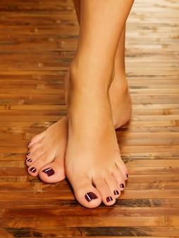 ペディキュア手順のスパサロンでの女性の足のクローズアップ写真-ソフトフォーカス画像